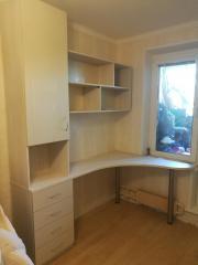 угловой письменный стол, распашной шкаф, тумба с выдвижными ящиками, навесные полки для книг.